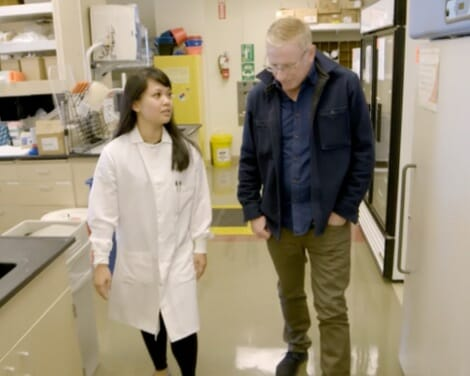 Man and scientist walking across a laboratory and talking