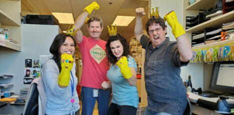 Coworkers wearing brightly decorated yellow gloves on one hand