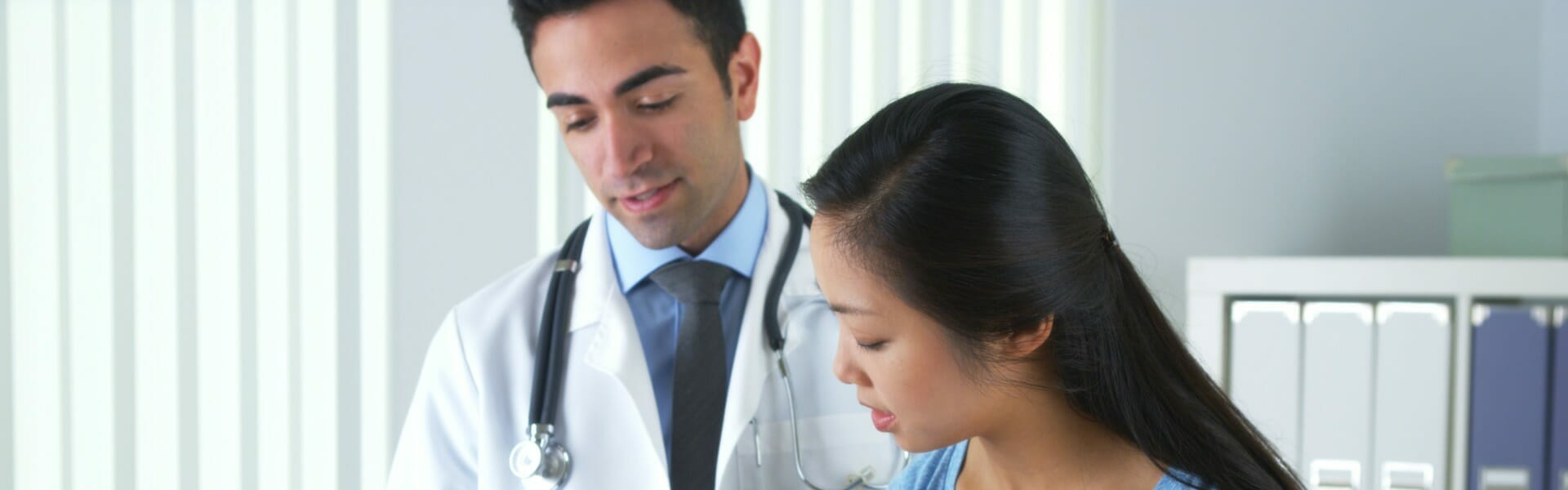A male healthcare professional speaking with a female patient